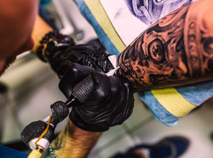 Professional tattooist creating a black and white detailed skull tattoo