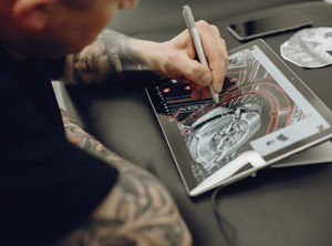 A tattooed man drawing a design on a tablet
